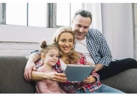 幸福家庭在客厅的沙发上使用数字平板电脑_3808446
