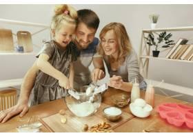 可爱的小女孩和她漂亮的父母在家里的厨房里_12699585