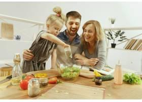 可爱的小女孩和她漂亮的父母在家里的厨房里_12699605
