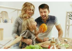 可爱的小女孩和她漂亮的父母在家里的厨房里_13056440