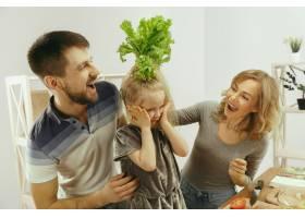 可爱的小女孩和她漂亮的父母在家里的厨房里_13056873