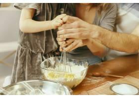 可爱的小女孩和她漂亮的父母在家里的厨房里_13341264