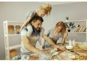 可爱的小女孩和她漂亮的父母在家里的厨房里_13341266