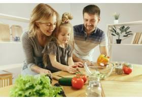 可爱的小女孩和她漂亮的父母在家里的厨房里_13341268