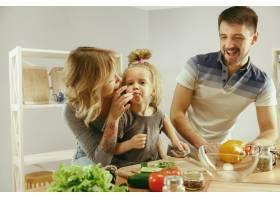 可爱的小女孩和她漂亮的父母在家里的厨房里_13341276