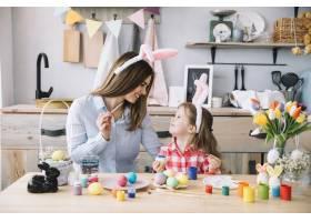 可爱的小女孩和妈妈一起画复活节彩蛋_3831189