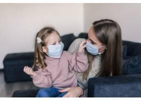 可爱的小女孩和戴着口罩的母亲坐在家里的_8471593