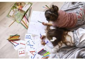 两个小女孩躺在毯子上的地板上画着涂色书的_7250340