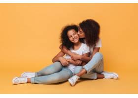 两个幸福的非洲姐妹坐在一起接吻_6873833