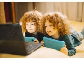两个拿着数字平板电脑的双胞胎小姐妹躺在床_3741363