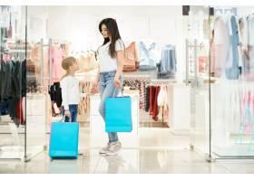 两个漂亮的顾客拿着购物袋在商店摆姿势_8792632