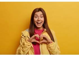 乐观的深色头发的年轻女子在胸前塑造了心形_13301375