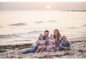 一个幸福的家庭在日落时坐在海边的特写镜头_11819333