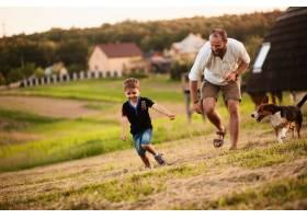 一个男人和他的儿子和一条狗在操场上玩耍_2915118