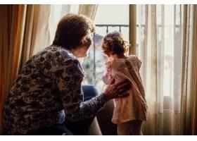 一位年长的女性和一个女婴透过窗户看着的美_7822839