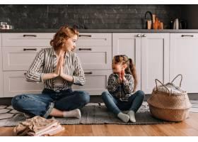 一位穿条纹衬衫的妇女坐在地板上教她的女_12677643