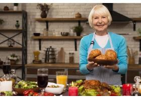 一位老妇人拿着一个装有面包的盘子看着相_5682544