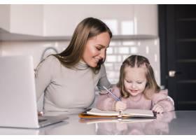 一位迷人的年轻女子和她可爱的小女儿坐在桌_8471491