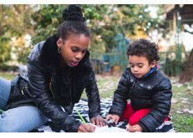 一位非裔美国母亲和他的儿子在公园里一起在_10104192