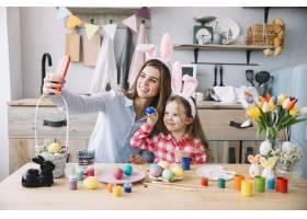 一名女子在复活节彩蛋附近与女儿自拍_3831197