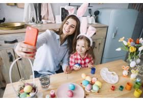 一名年轻女子在复活节彩蛋附近与女儿自拍_3831200