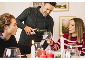 一名男子在圣诞晚宴上加满酒杯_1400608