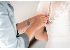 一名男子帮助她的妻子穿着婚纱的特写镜头_13617939