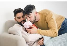 一名男子看着他的男朋友亲吻他们熟睡的婴儿_4105408