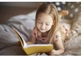 小女孩在床上读书的特写肖像_13249607