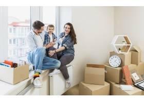 幸福的一家人坐在新家的窗台上搬着纸箱_3951144