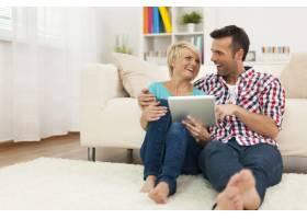 幸福的夫妇坐在家里的地毯上使用数字平板电_10675041