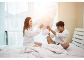 幸福的年轻夫妇在床上玩得很开心_3398369