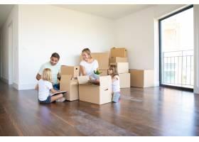 幸福的父母和两个孩子搬进了新的空荡荡的公_10608477