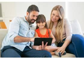 幸福的父母和可爱的女儿坐在沙发上用平板_9988537