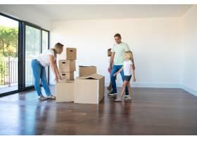 幸福的父母和女儿在新的空荡荡的公寓里打开_10608469