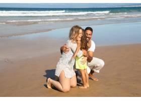 幸福的父母在海上潮湿的沙滩上拥抱小女儿_10608478