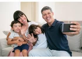 幸福的父母拥抱可爱的孩子一起坐在家里的_9988540