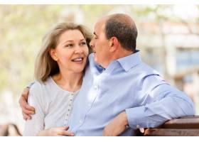 幸福的老年夫妇在长凳上拥抱_1474856