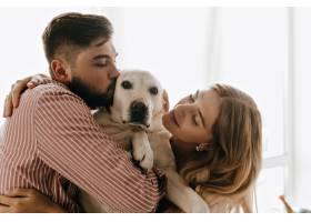 心情愉快的浪漫情侣玩耍拥抱白狗一名男子_12432023