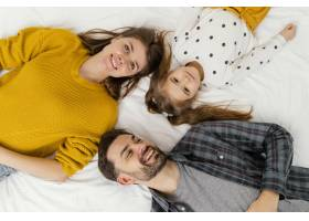 中等镜头的父母和孩子在床顶视图中_12553001