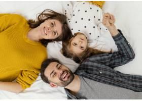 中等镜头的父母和孩子平躺在床上_12553009