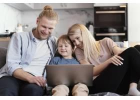 中景笑脸带笔记本电脑的父母和孩子_13436826