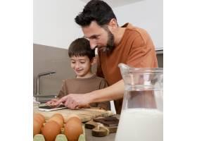 中等射击的男人和孩子在厨房里拿着平板电脑_13402828