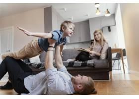 中等射程的父亲和孩子在家中玩耍_13436819