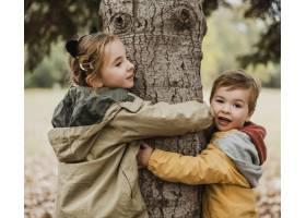 中等镜头的孩子们拥抱着树_11103644