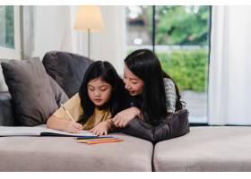 亚洲中年妇女在家教女儿做作业和画画生活_6142488