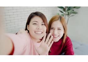 亚洲博主女性在家中的起居室使用智能手机自_4015341