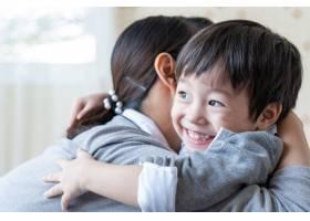 亚洲可爱男孩开心微笑在家中与母亲拥抱_5388956
