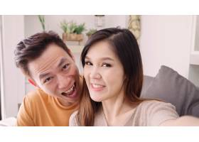 亚洲夫妇在家中客厅与朋友使用智能手机视频_4015343