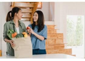 亚洲女同性恋LGBTQ女性夫妇在家中拿着杂货_5503728
